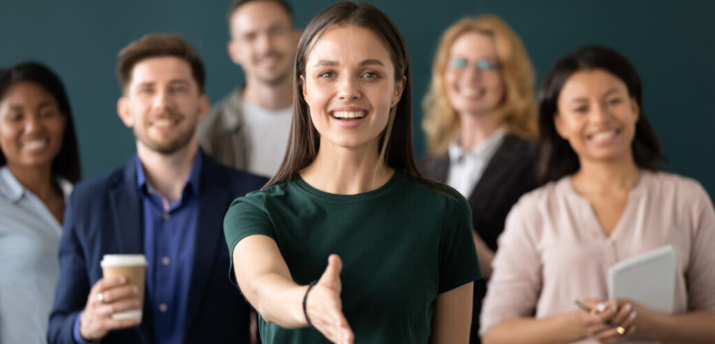 Woman company representative holds out hand for handshake welcoming client